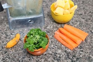 Carrots, parsley, turmeric and mango in measuring cups around a blender