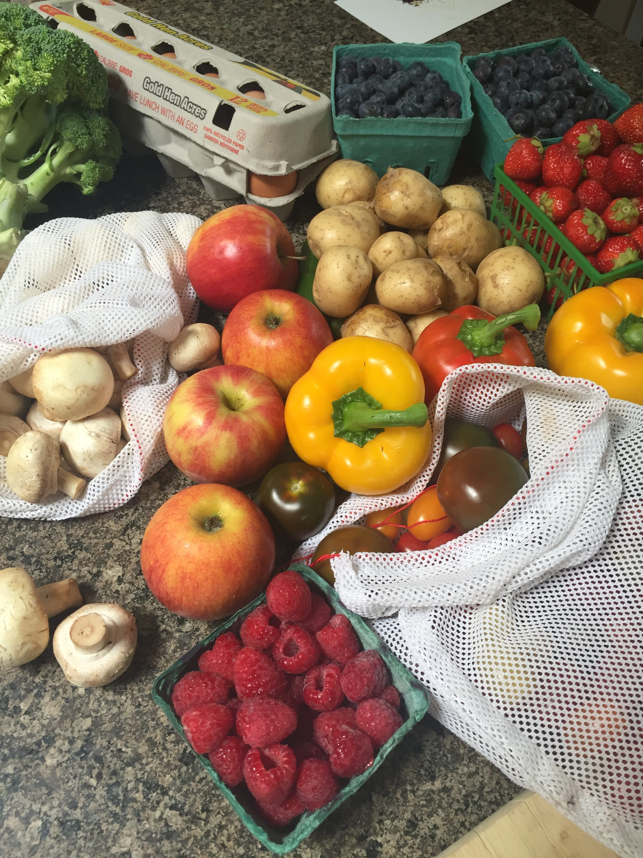 A mix of colorful fruits and veggies like apples, peppers, mushrooms and berries with tomatoes in reusable produce bags