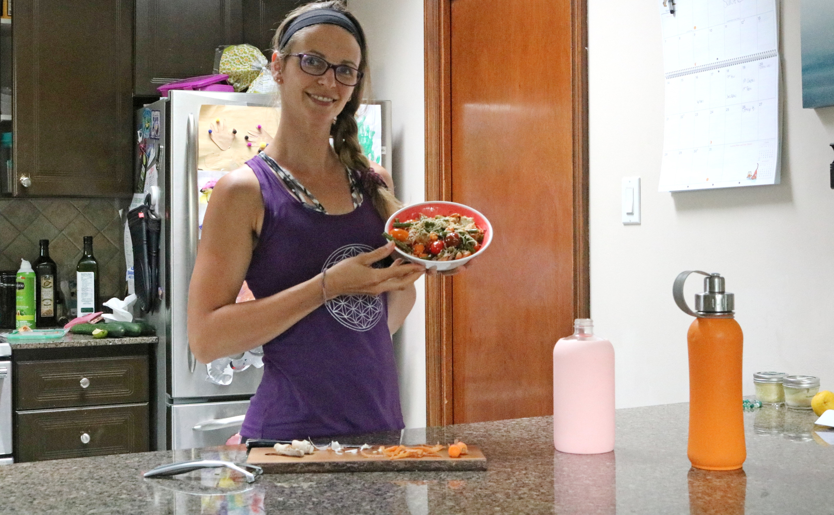 Women in purple shirt standing in kitchen holding a bowl of healthy food