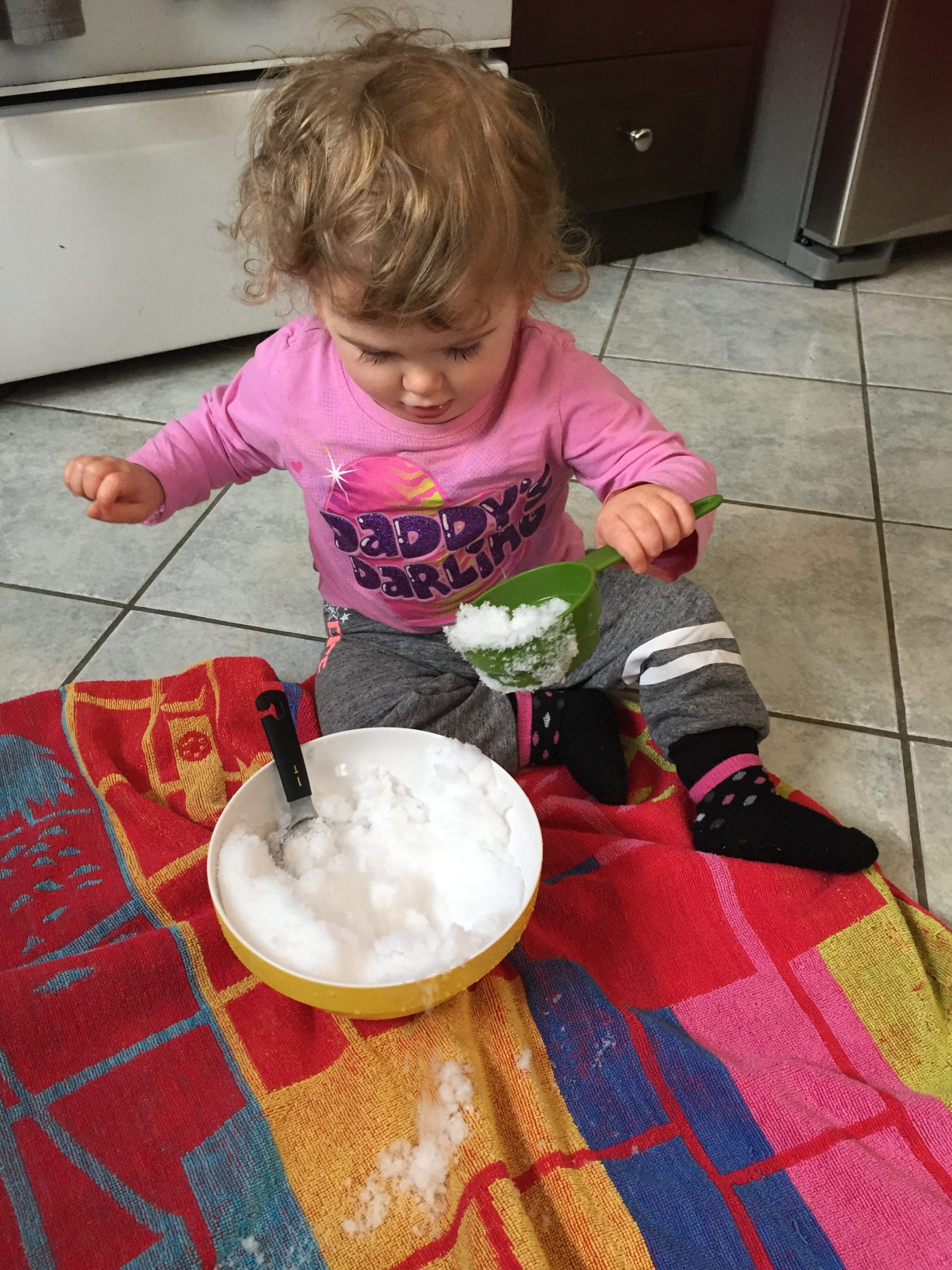 Toddler in pink shirt, grey pants scooping snow from a bowl with a measuring cup