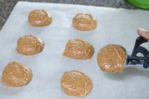 Inprocess image: Gluten-free cashew cookies raw on a piece of parchment paper