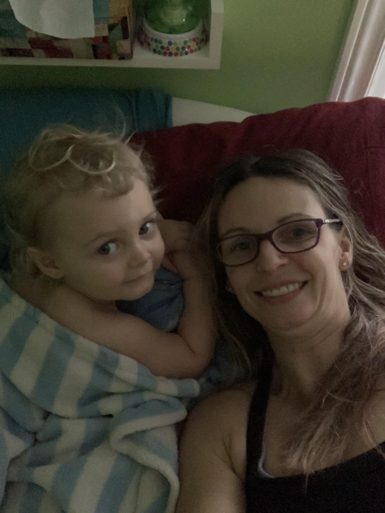 Mom and toddler snuggling together in bed