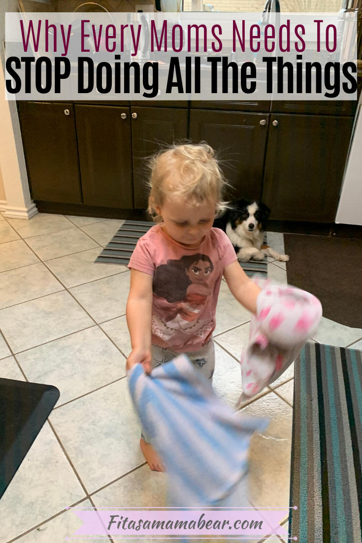 Pinterest image with text: a toddler in a pink shirt in the kitchen playing with blankets