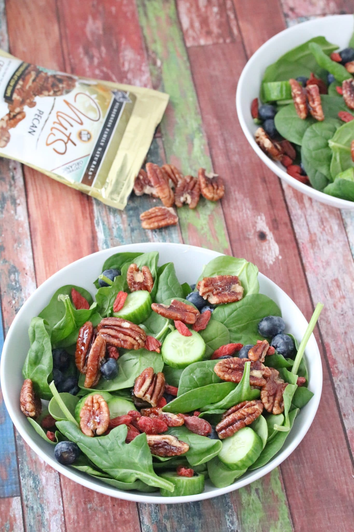 Spinach salad with pecans in a white bowl with another bowl of salad behind it and pecans on the table