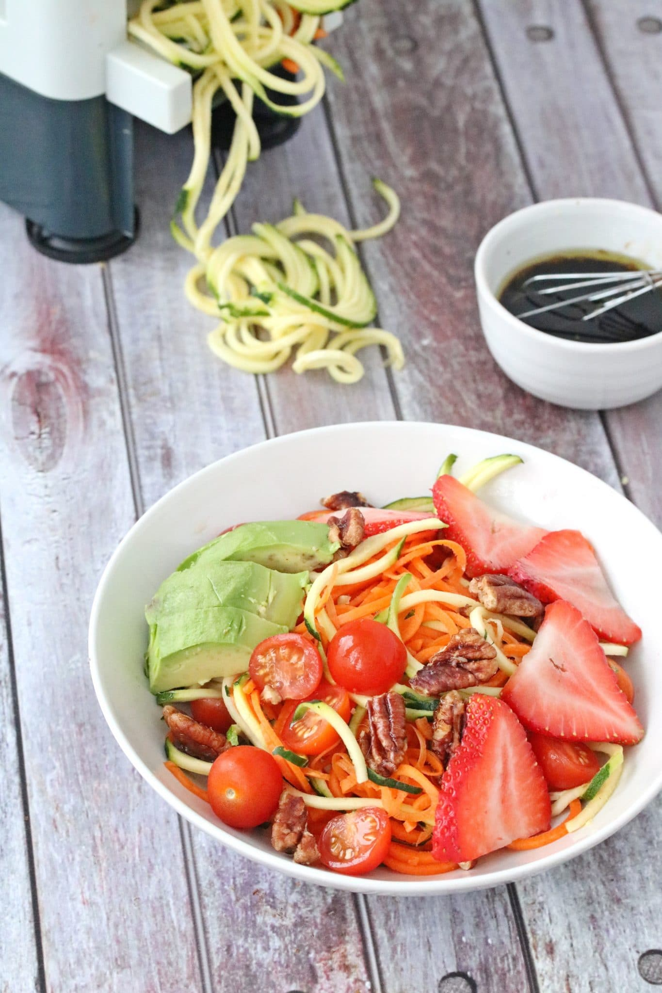Spiralized zucchini salad topped with strawberries, avocado and pecans with dressing and zucchini noodles behind it