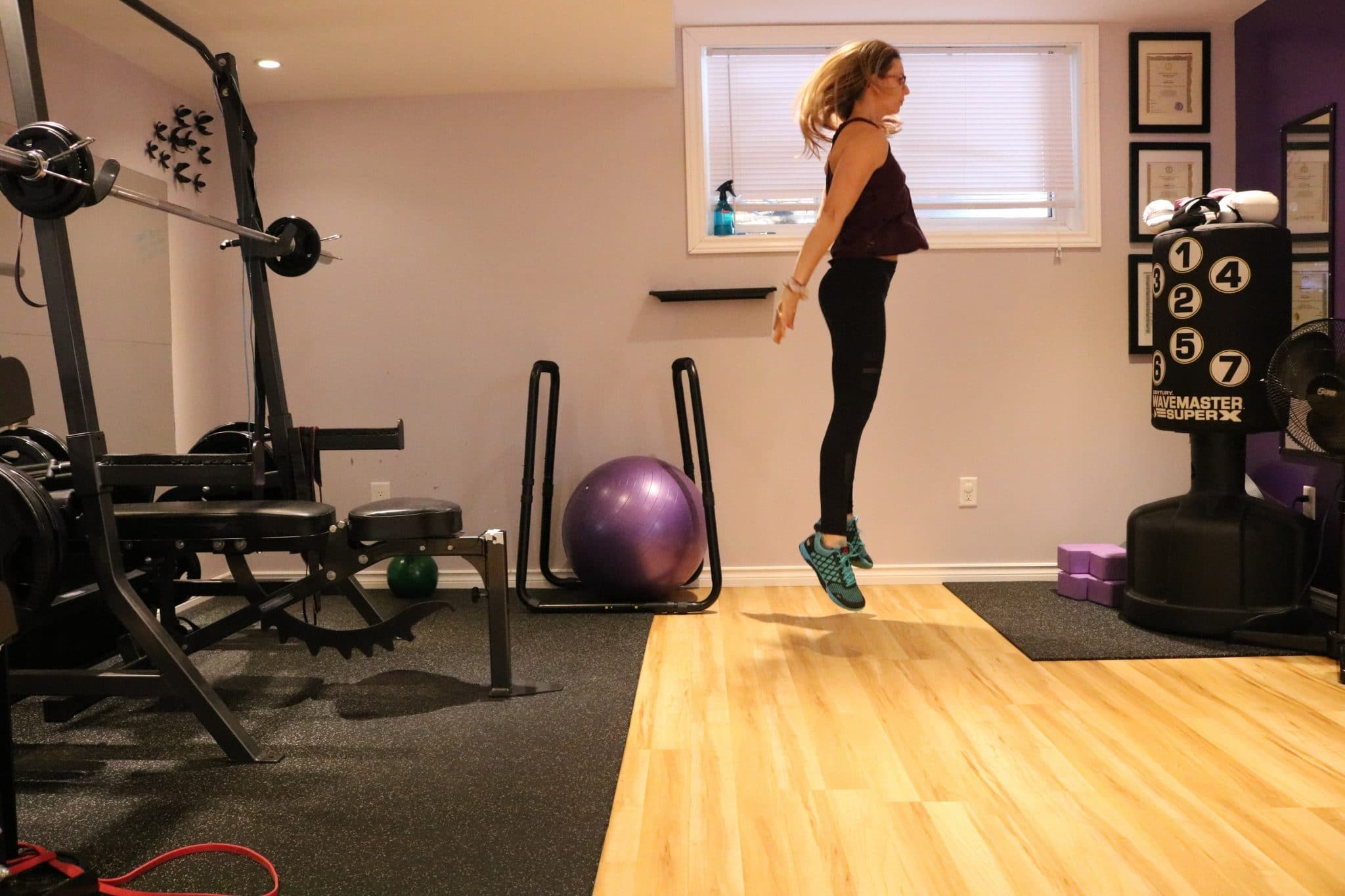 Woman in dark fitness clothes at the top of a jump in a gym