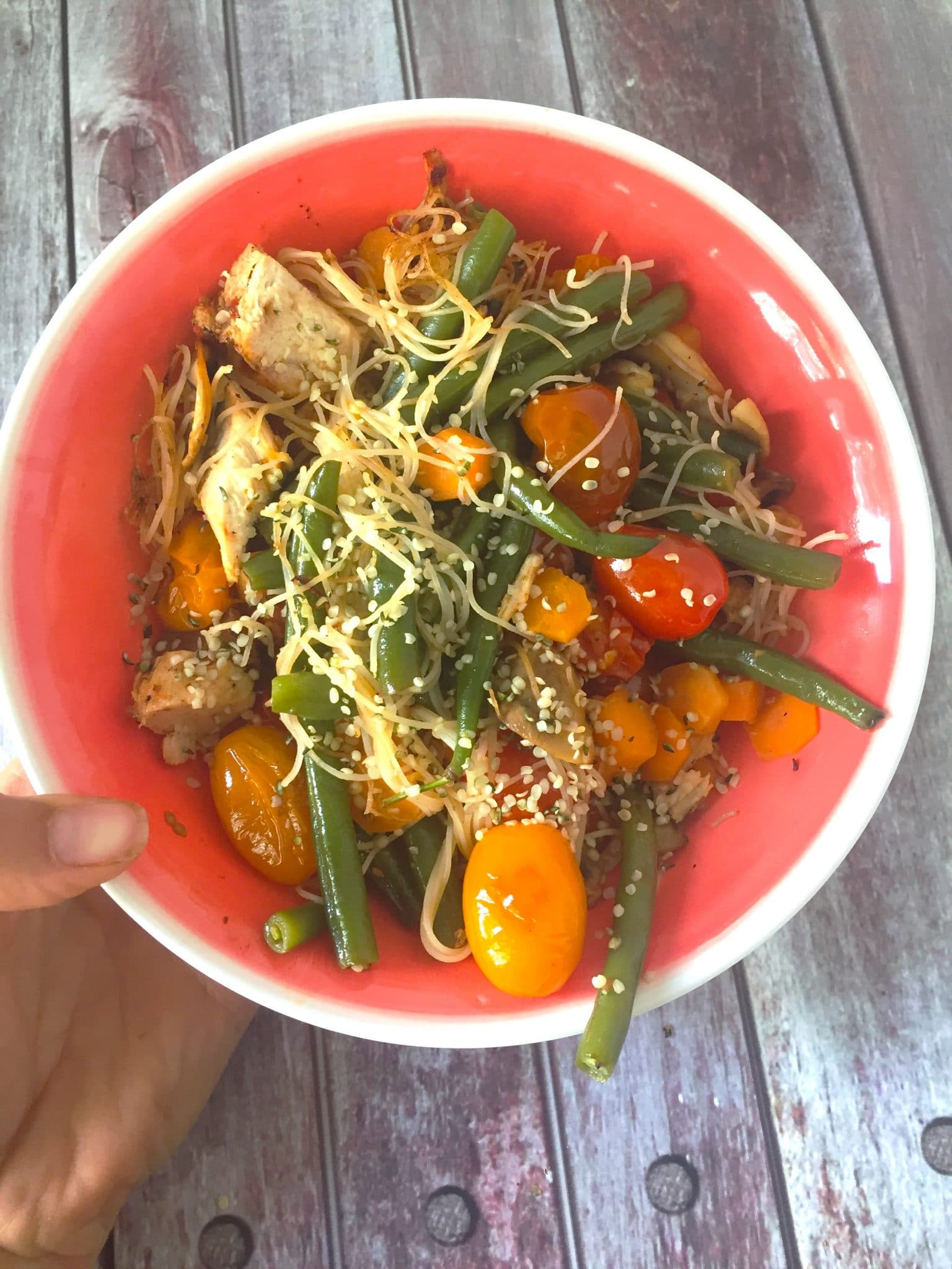 A red bowl with noodles, tomatoes and snap peas mixed together for lunch