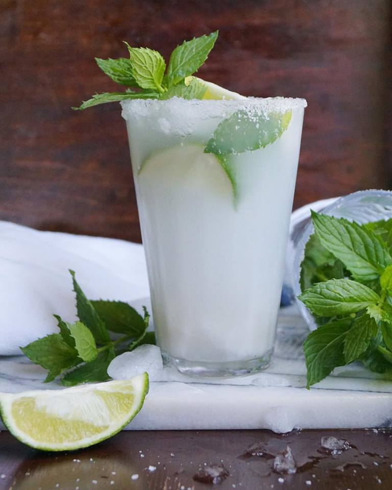Coconut mojito mocktail recipe. Mocktail in a tall glass with mint and lime on and around it