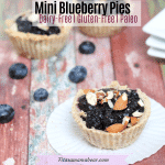Featured image with text: blueberry tart on a white muffin cup with blueberries, more tarts and plates behind it