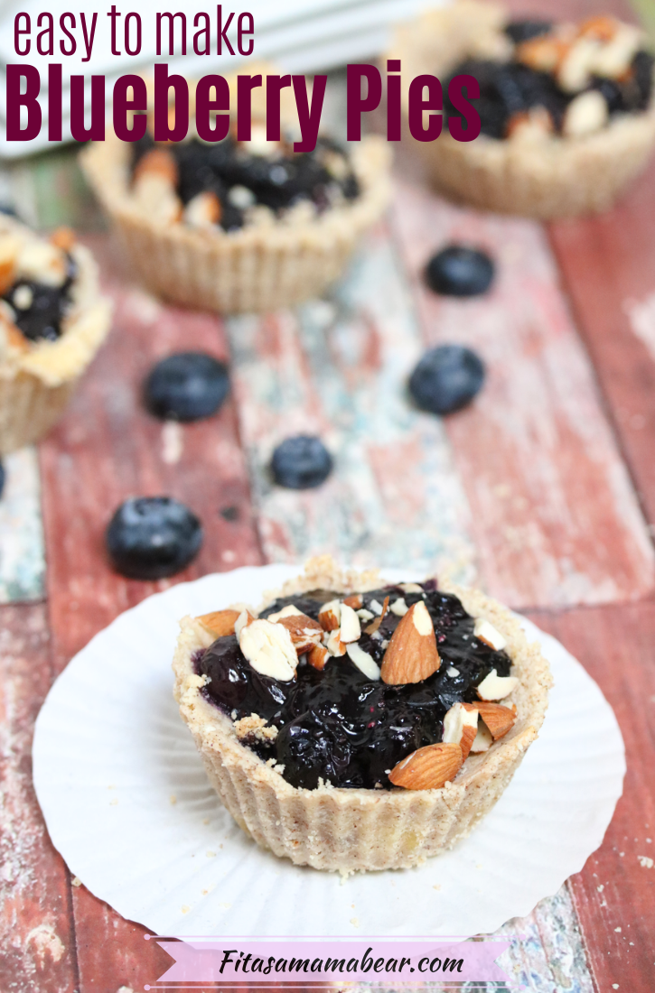 Pinterest image with text: blueberry tart on a white muffin cup with blueberries, more tarts and plates behind it