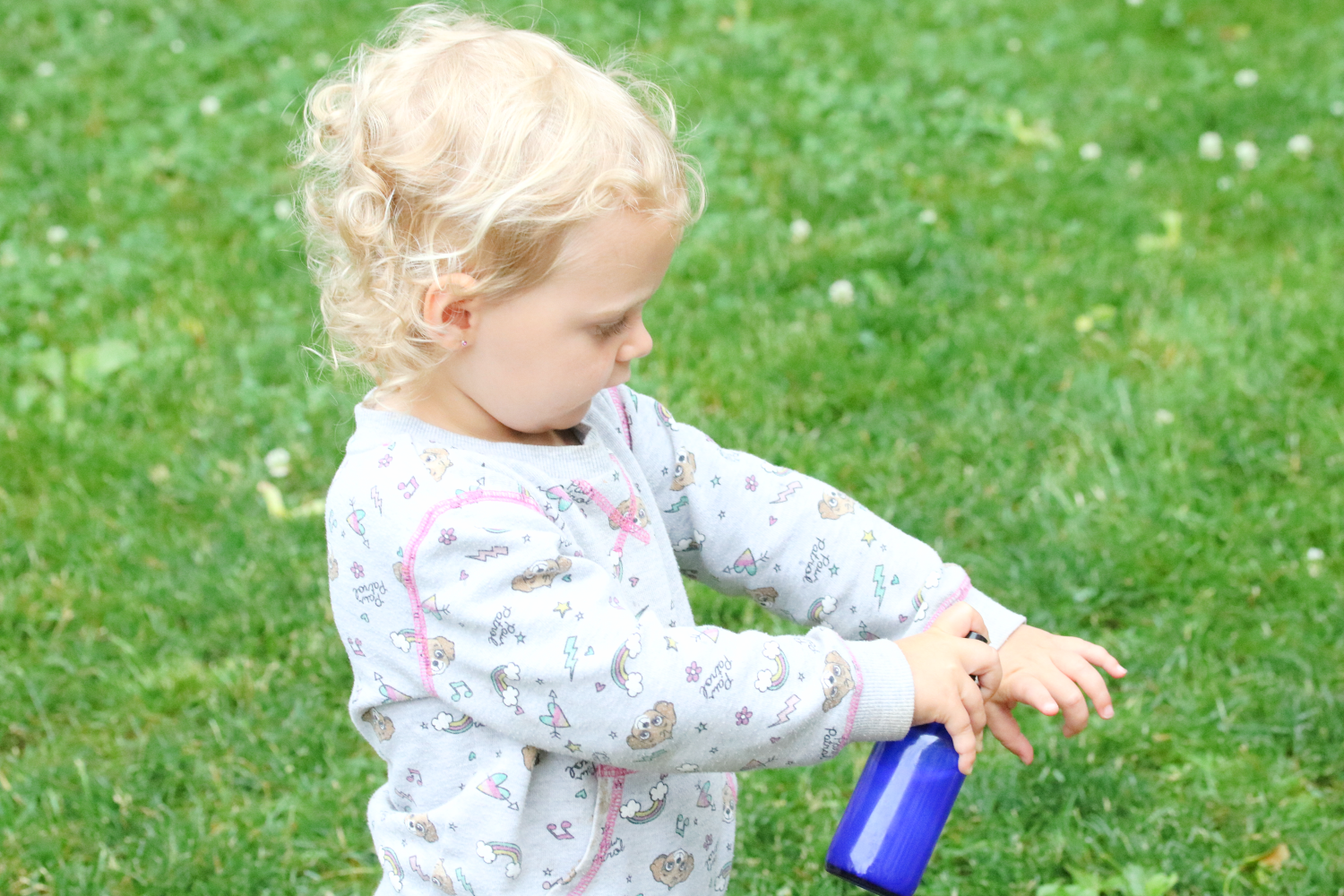 Toddler dressed in grey sweater spraying a blue glass bottle on her arm