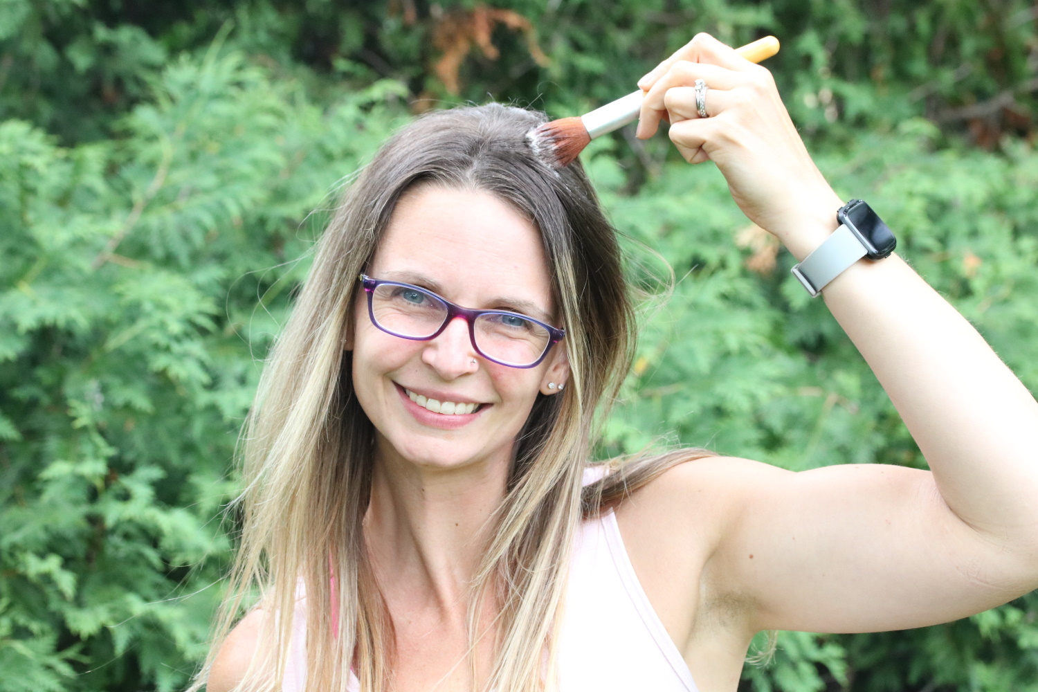 Woman outside in peach shirt using a makeup brush to distribute dry shampoo into her hair