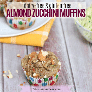 Featured image with text: almond zucchini muffin in a polkadot muffin cup in front of more muffins on a white plate and yellow napkin