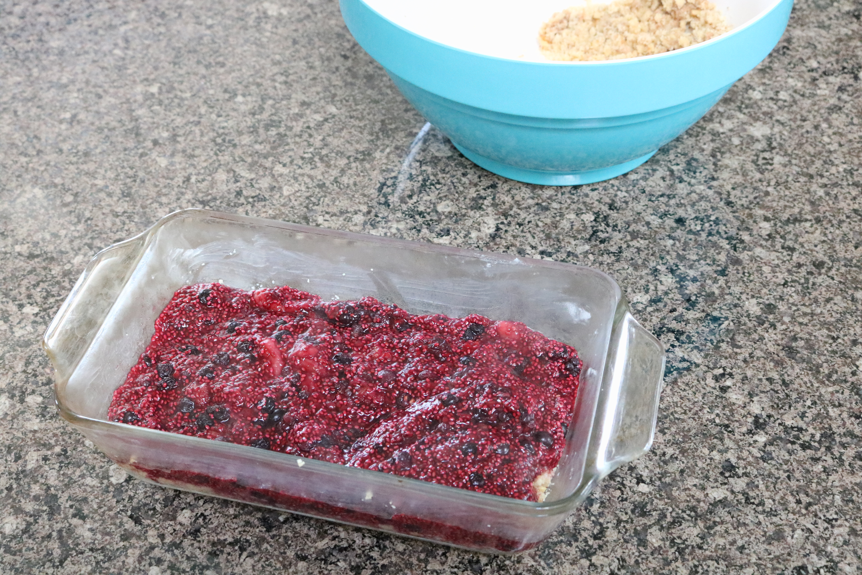 Berry crisp in a glass dish with a blue bowl of ingredients behind it