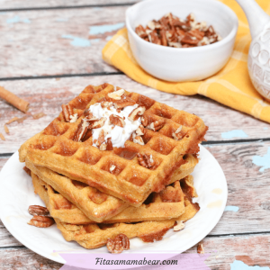 Pinterest image with text: three paleo pumpkin waffles stacked on a white plate with syrup and coconut milk. Pecans and syrup in white dishes on a yellow cloth behind them.