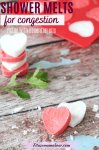 Pinterest image with text: two heart shaped DIY shower melts in red and white stacked with more melts stacked behind them and a sprig of mint and a silicone mold of shower steamers at the back