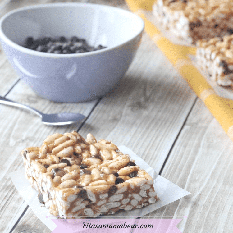 Featured image with text: healthy rice krispie square on parchment paper with a bowl of chocolate chips, a small spoon and more squares behind it