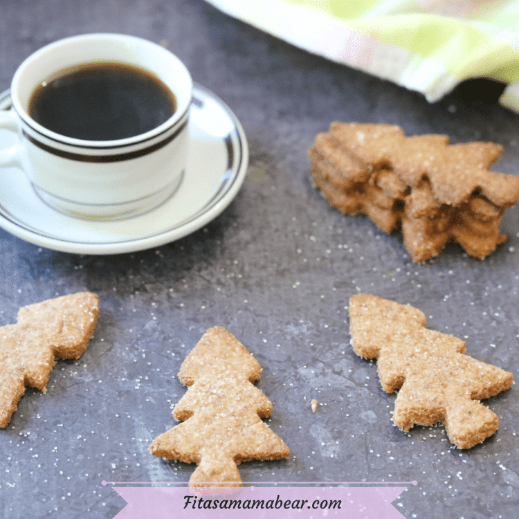 Featured image with text: almond flour sugar cookies in the shape of Christmas trees around a white mug of coffee on a saucer