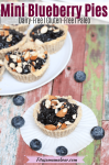 Pinterest image with text: blueberry maple mini tart on a white cupcke liner with blueberries around it and more tarts on a white plate behind it