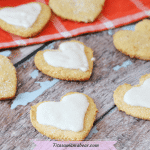 Featured image with text: coconut flour sugar cookies in the shape of hearts, half with white icing on an orange linen