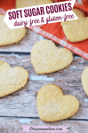 Pinterest image with text: coconut flour sugar cookies in the shape of hearts on an orange linen