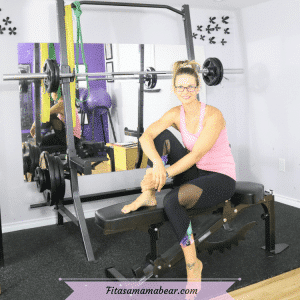 Featured image of a woman in a pink shirt and black pants sitting on a workout bench in the gym