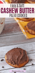 Pinterest image with text: paleo cashew butter cookie frosted with chocolate with a mug and more cookies behind it