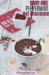 Pinterest image with text: dairy-free hot chocolate in a white snowman mug, topped with coconut milk and with a candy cane in it and candy canes behind it