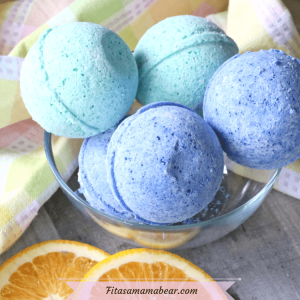 Featured image: blue and green bath bombs in a glass bowl with a yellow linen and oranges around the bowl