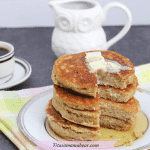 Featured image: four dairy-free pancakes stacked on a plate with syrup and butter with the plate on a colorful linen and coffee behind the plate
