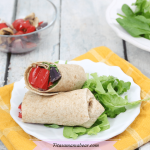Featured image: two veggie wraps on a white plate with lettuce with grilled vegetables and salad behind it and a yellow linen under it