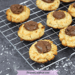 Featured image with text: coconut almond cookies with chocolate on a cooling rack with shredded cocnut below it