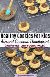 Pinterest image with text: two images, the top a healthy thumbprint cookie surrounded by coconut and more cookies the bottom with cookies on a cooling rack