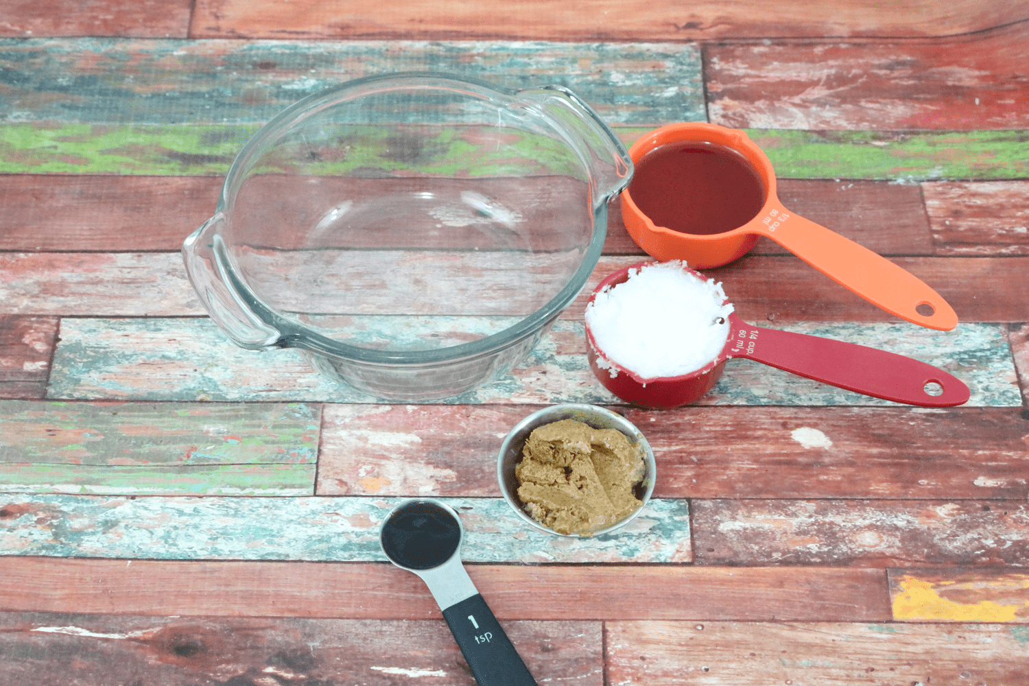 multiple granola ingredients in measuring cups all place around a glass bowl