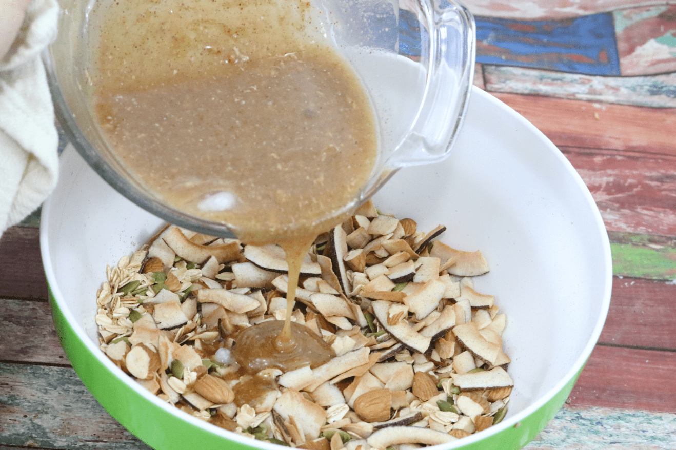 melted almond butter and maple syrup in a glass bowl being poured into toasted coconut and nuts in a green mixing bowl
