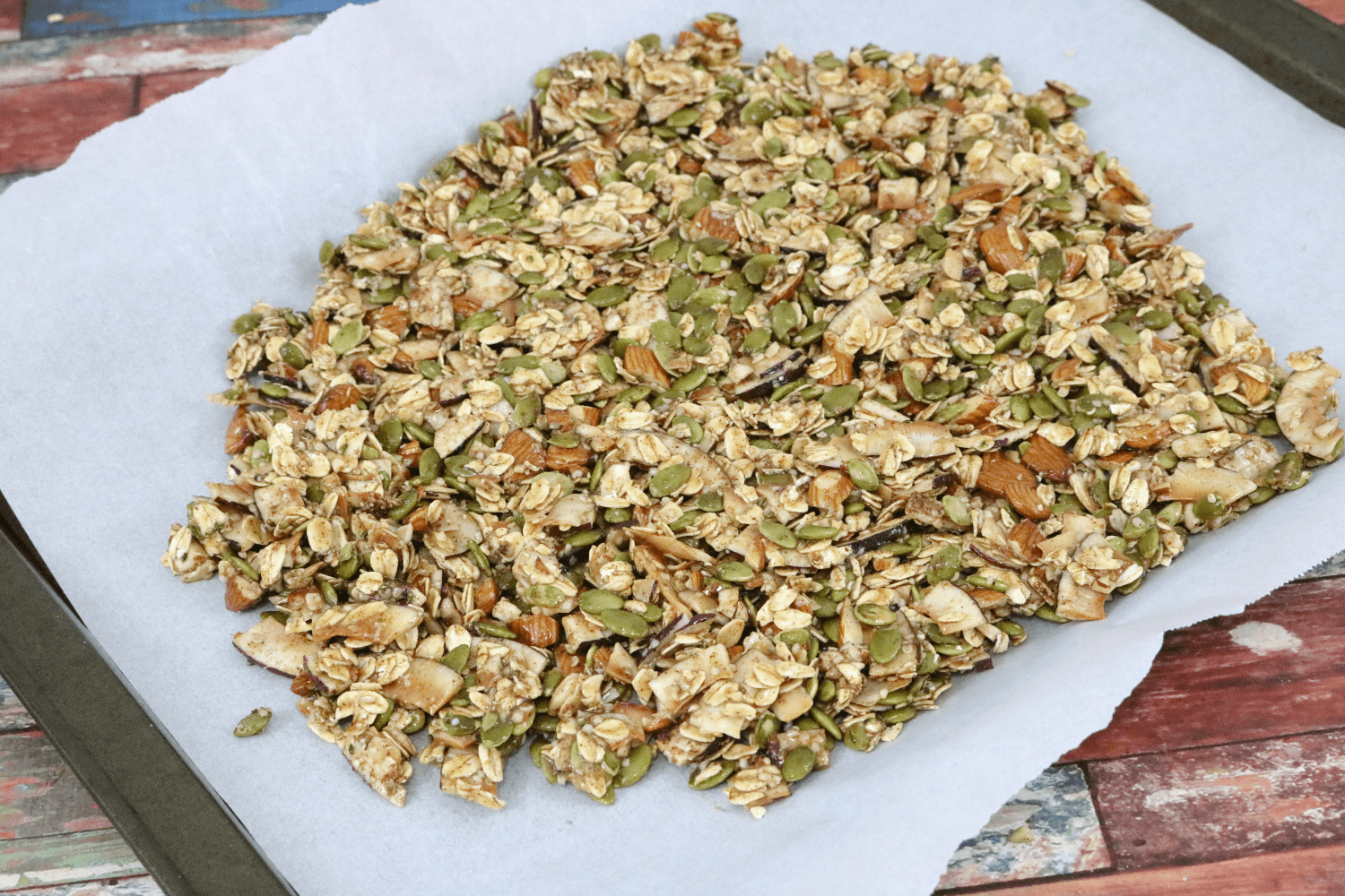 Homemade granola on a baking tray lined with parchment paper