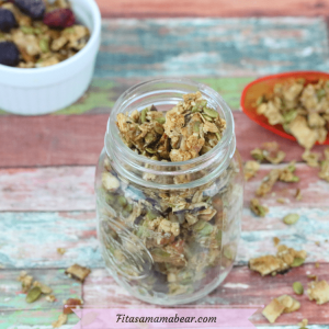 featured image: homemade crunchy granola in a mason jar with more granola in a white ramekin and an orange scoop behhind it