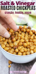 Pinterest image with text: salt and vinegar roasted chickpeas in a white bowl with a hand grabbing for them
