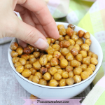 Featured image with text: salt and vinegar roasted chickpeas in a white bowl with a hand grabbing for them