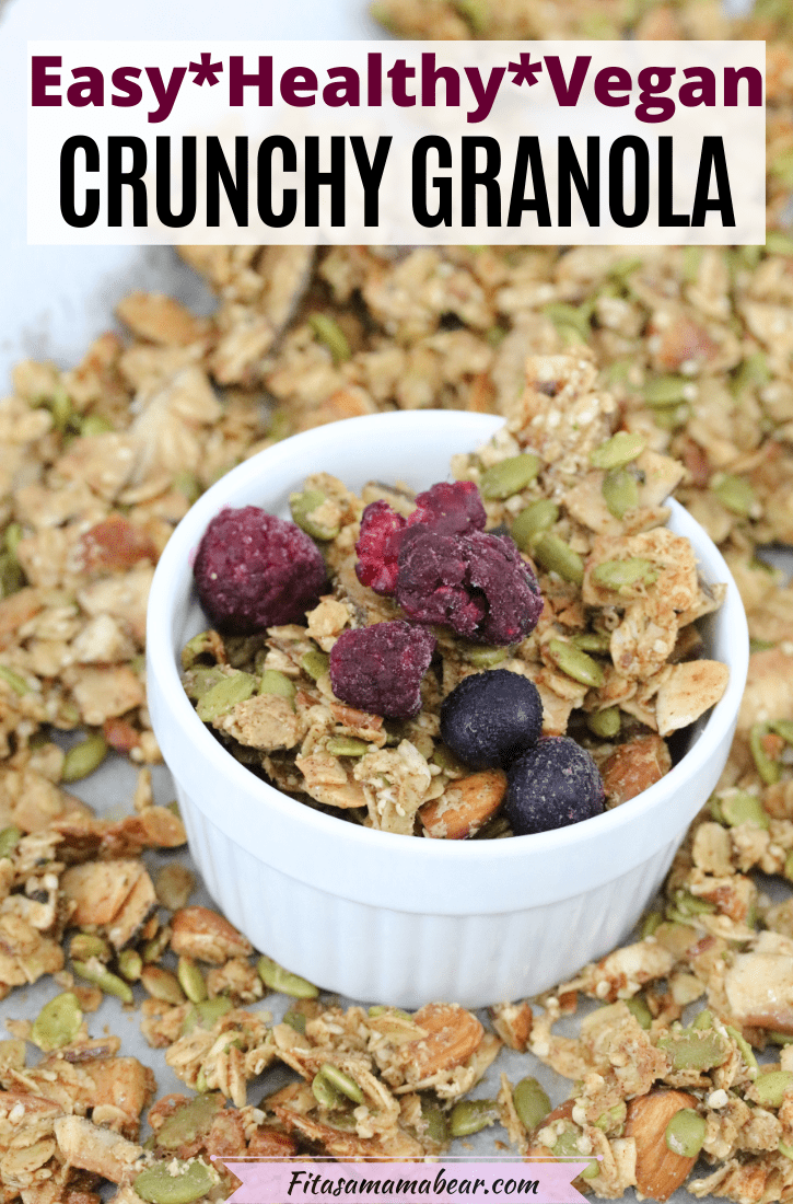 Pinterest image with text: homwmade crunchy granola in a white ramekin sitting on the baking sheet and frozen berrie son top