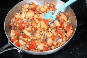 Stainless steel pan on a black stove with mushrooms, potatoes, red peppers, salsa and chickpeas in it with a blue spatula