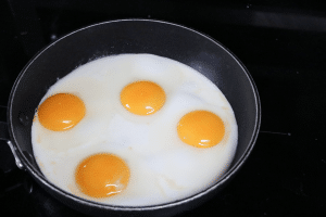 Black pan on a black stove with four eggs being cooked in it
