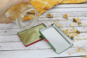 Hand holding a mason jar pouring melted lotion into a red and green tin surrounded by dried flowers and a yellow linen