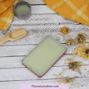 Featured image with text: homemade nipple cream in a tin with dried herbs, a wooden spoon and herb infused oil around it