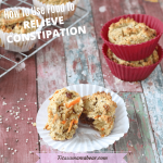Pinterest image with text: carrot muffin broken in half on a white muffin cup with muffins in red muffin holders and on a cooling rack behind it