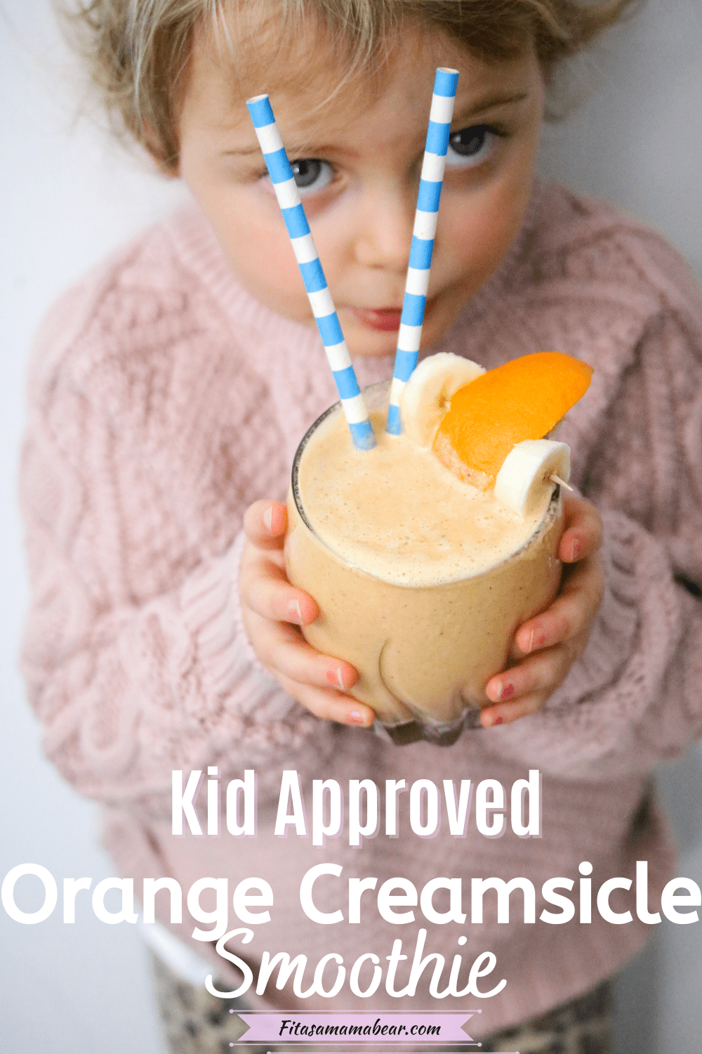 Pinterest image with text: toddler in pink sweater holding an orange creamsicle smoothie in a glass with blue straws
