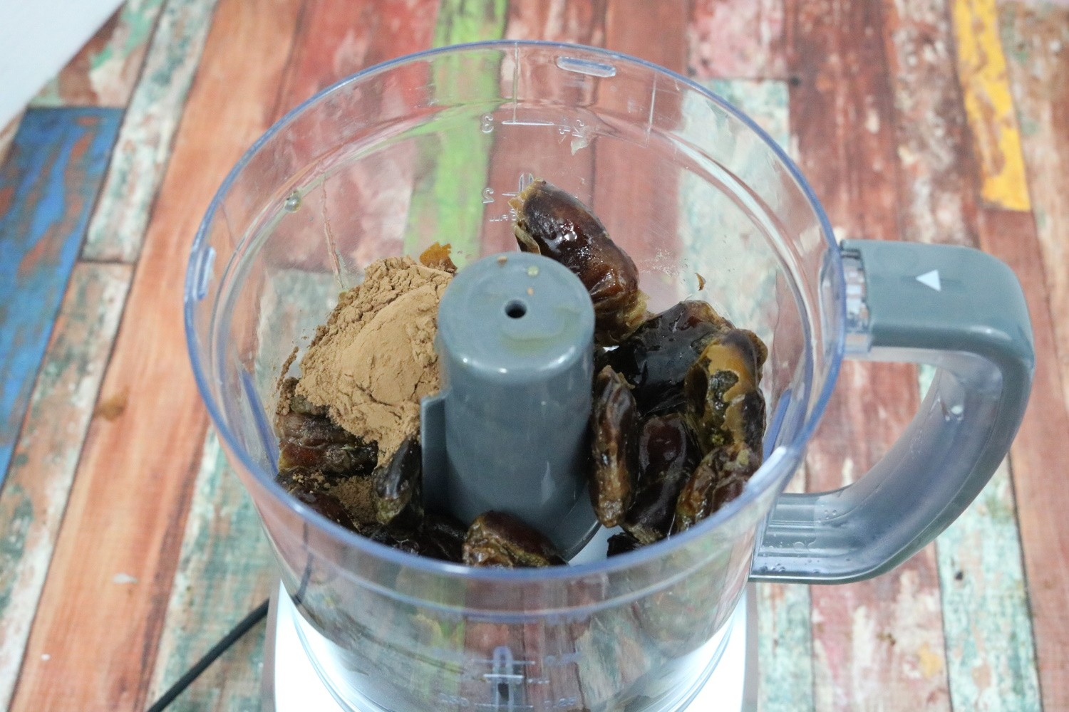 a mini food processor with dates and cacao powder in it