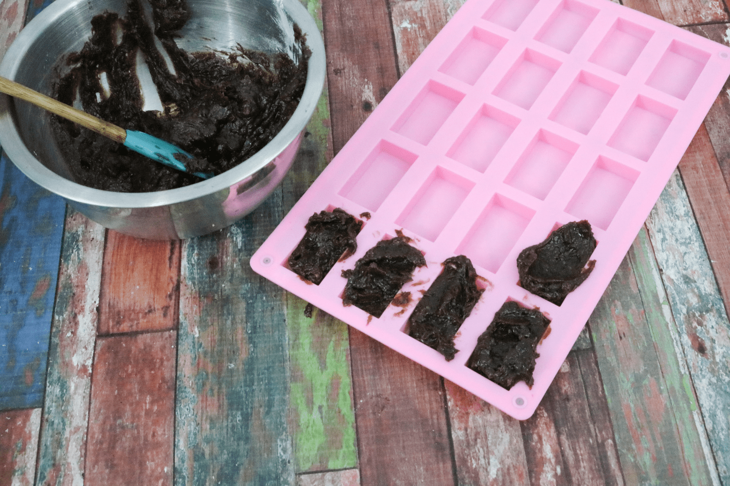 Pink silicone mold being filled with homemade snickers base with more mix in a steel bowl beside it