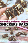 Pinterest image with text: two images of homemade snickers bars, the top image of two fingers holding up one bar the bottom image of multiple bars with more in a pink mold behind it