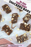 Pinterest image with text: multiple homemade snickers bars topped with caramel sauce on parchment paper with peanuts sprinkled around